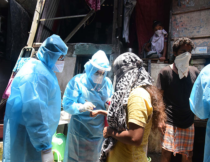 Health workers wearing protective suits screen resident of Dharavi in Mumbai during a house-to-house health survey. Photograph: PTI Photo