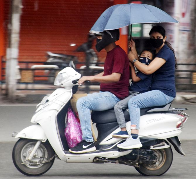 A family use umbrella to protect themselves from rain as they walk to home on a two-wheeler during the nationwide lockdown to curb the spread of coronavirus in Guwahati on Tuesday. (ANI Photo)