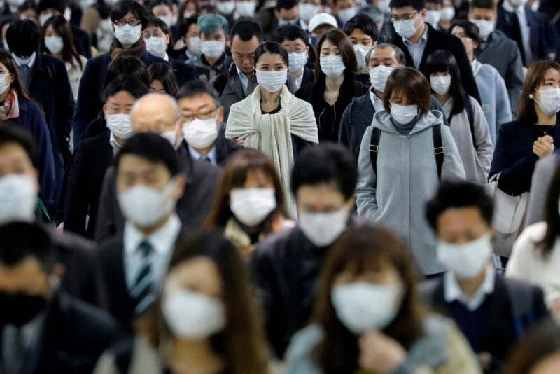 FILE PHOTO: People wear face masks at Shinagawa station during the rush hour after the government expanded a state of emergency to include the entire country following the coronavirus disease (COVID-19) outbreak, in Tokyo, Japan, April 20, 2020. REUTERS/K