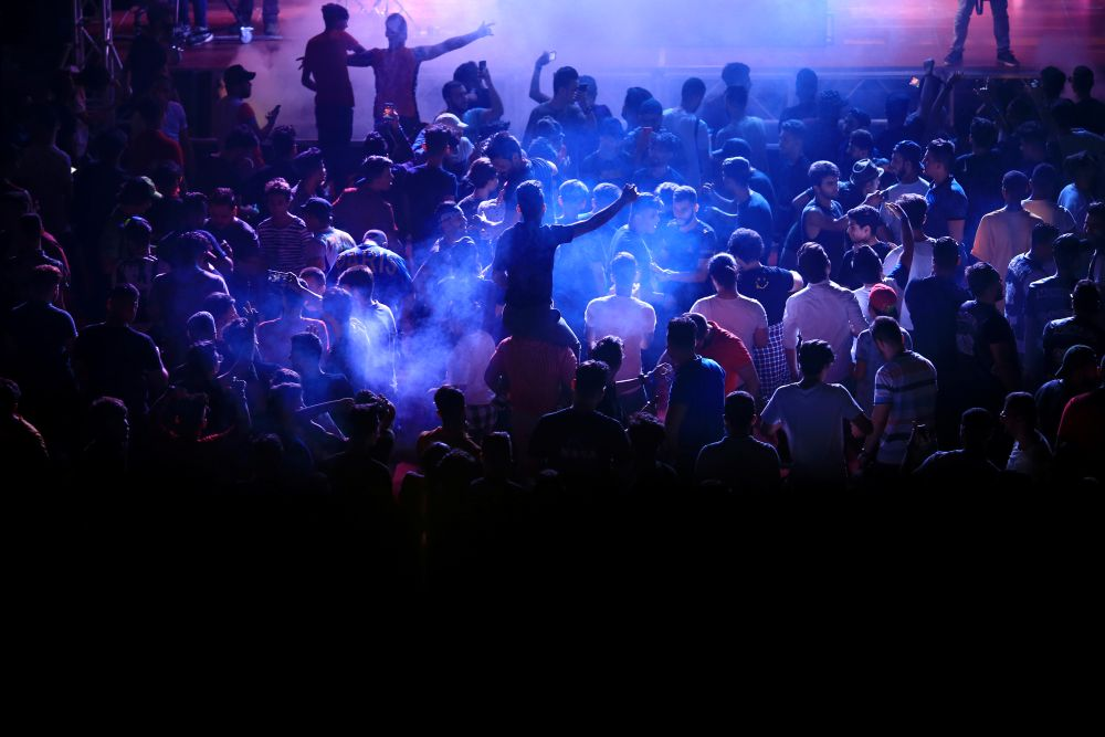 Young people dance as they attend electronic music concert with western tunes at closed Hall in Shaab Stadium for the first time in Baghdad, Iraq August 16, 2019. Picture taken August 16, 2019  REUTERS/Thaier Al-Sudani