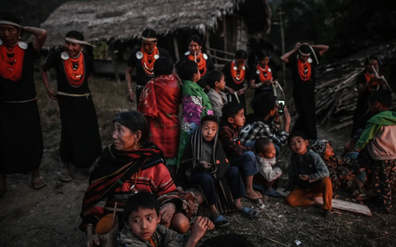 Naga women and children sit by a fireside during an overnight ceremony
