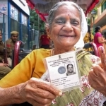 A elderly woman holds her voter identity card as she shows her inked finger after casting vote during the bye-poll of Mahalaxmi Layout constituency, in Bengaluru, Thursday, Dec. 5, 2019. (PTI Photo)