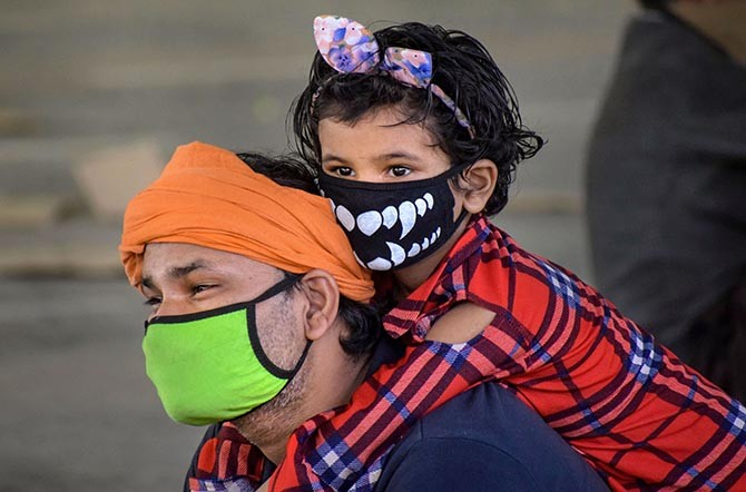 A migrant carrying his daughter waits for registration to board a bus to reach his native place after arriving from Mumbai via special train at Praygraj railway station, during the ongoing COVID-19 lockdown, in Prayagraj, Tuesday, May 26, 2020. (PTI Photo)