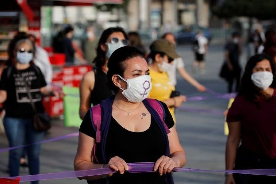 Women wearing protective face masks keep social distance by holding onto purple ribbons as they protest for women rights and against child abuse, amid the spread of the coronavirus disease (COVID-19), in Istanbul, Turkey, May 20, 2020. REUTERS/Umit Bektas