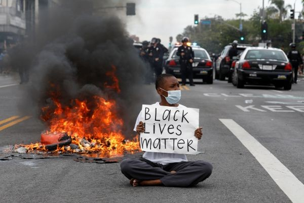 A demonstrator holds a placard during a protest against the death in Minneapolis police custody of George Floyd, in Los Angeles, California, U.S., May 30, 2020. (REUTERS Photo)