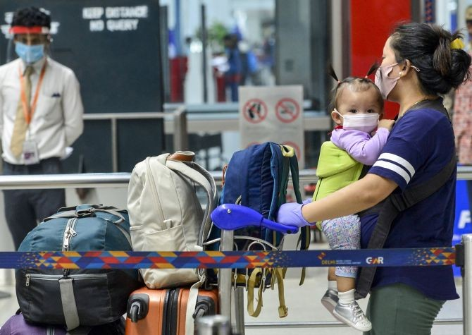 A woman carrying a child arrives at T-3 airport for domestic travel, after flights were resumed, in New Delhi, Monday, May 25, 2020. All scheduled commercial passenger flights were suspended since March 25 when the government imposed a nationwide lockdown to curb the coronavirus pandemic. (PTI Photo/Kamal Kishore)