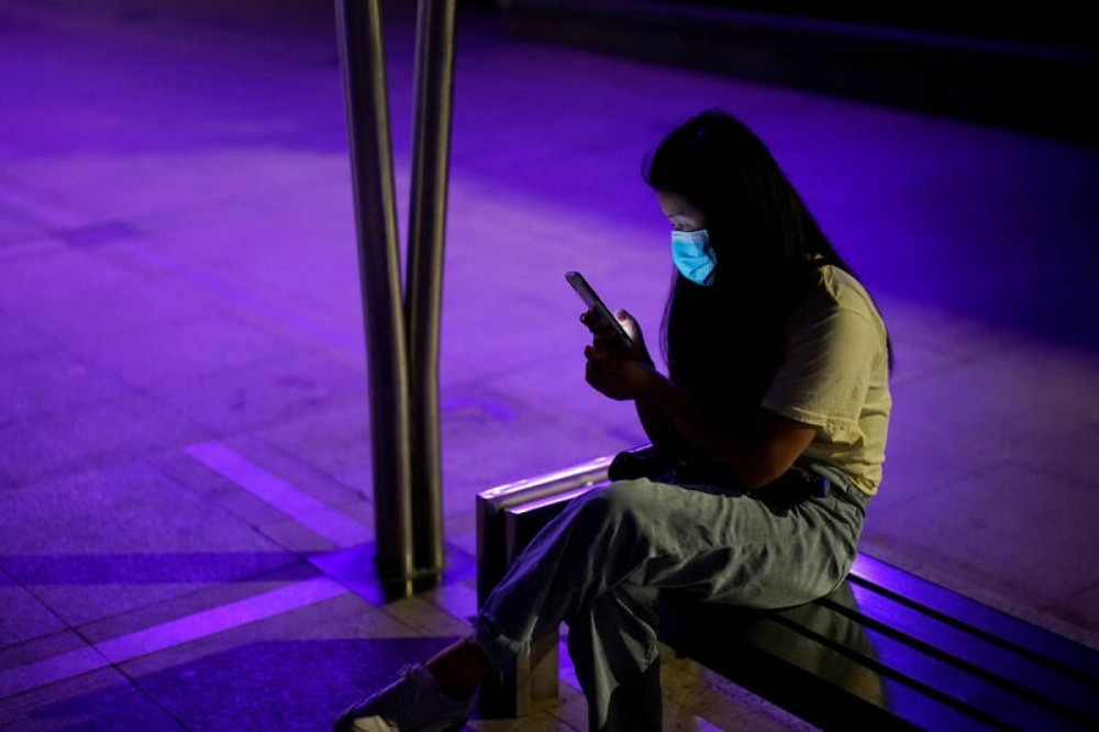 A woman wearing a protective face mask uses a phone at a park in Wuhan, the Chinese city hit the hardest by the coronavirus disease (COVID-19) outbreak, in the Hubei province, China, May 15, 2020. REUTERS/Aly Song