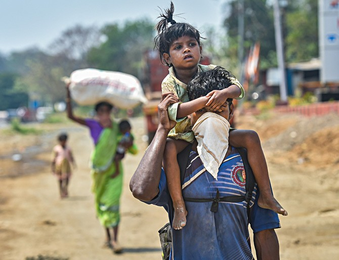 A migrant worker and his family walk to their village in the summer heat along the Mumbai-Ahmedabad highway in Palghar, Maharashtra, following the coronavirus-provoked lockdown. Photograph: Mitesh Bhuvad/PTI Photo