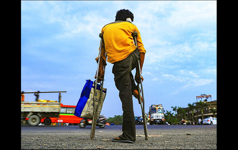 A physically challenged migrant waits for transportation in Ahmedabad. Photograph: PTI Photo