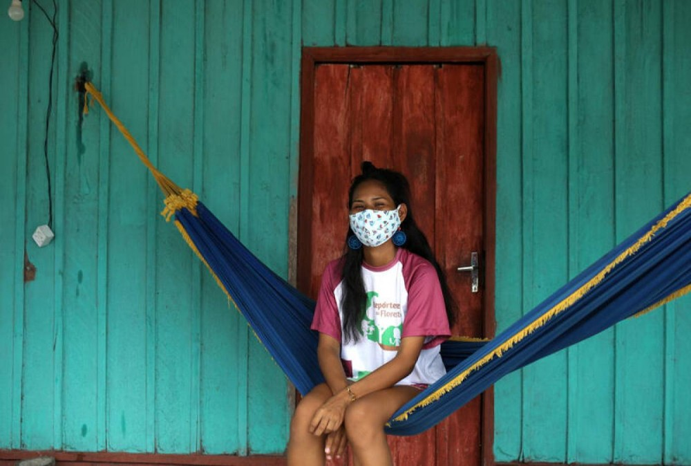A Kambeba indigenous woman, wearing a protective face mask, sits as she waits to be tested for the coronavirus disease (COVID-19), on the banks of the Negro river at the village Tres Unidos, Amazon state, Brazil, May 21, 2020. Picture taken May 21, 2020. REUTERS/Bruno Kelly