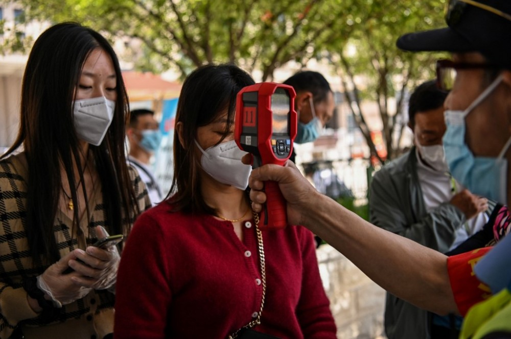 A worker wearing a face mask checks passengers body temperatures and a health code on their phones before they take a taxi after arriving at Hankou railway station in Wuhan, China's central Hubei province . Photo by Hector Retamal/AFP