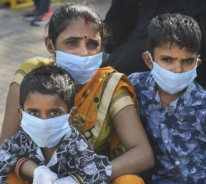 Migrants, wearing masks, wait to get medically screened before boarding a train for their native places in Bihar and UP, in New Delhi, on Monday. Photograph: Arun Sharma/PTI Photo