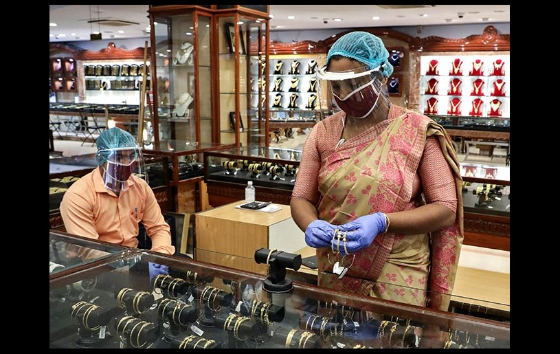A sales woman wearing a face shield and a mask arranges gold bangles at a jewellery showroom as few stores opened after few restrictions were lifted in Kolkata. Photograph: Rupak De Chowdhuri/Reuters