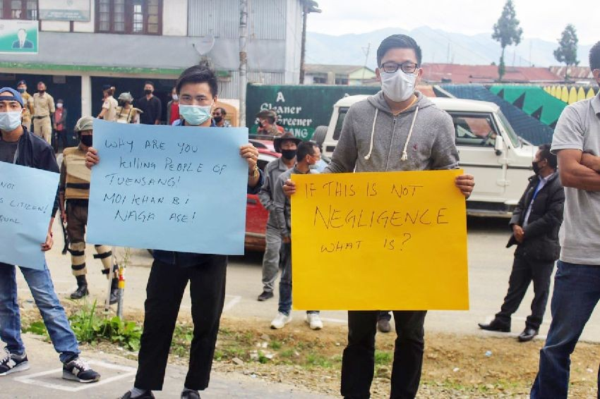 People holding placards protesting against the government's apparent mismanagement  of returnees.   (Morung Photo)