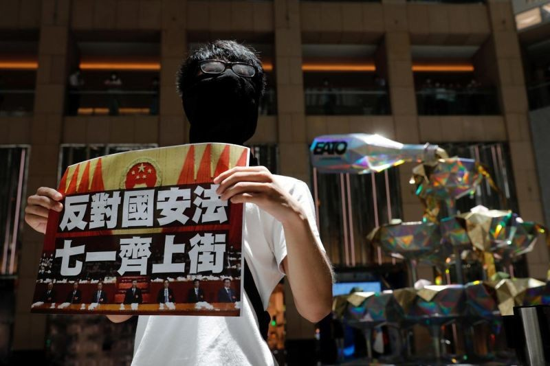 A pro-democracy protester holds a placard that reads ''Against the national security law. March on July 1'' during a protest after China's parliament passes a national security law for Hong Kong, in Hong Kong, China on June 30. (REUTERS  Photo)