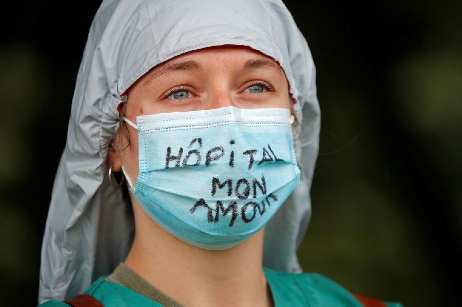 "A French health worker attends a protest in Paris as part of a nationwide day of actions to urge the government to improve wages and invest in public hospitals, in the wake of the coronavirus disease (COVID-19) crisis in France June 16, 2020. The slogan reads ""Hospital my love"". REUTERS/Charles Platiau"