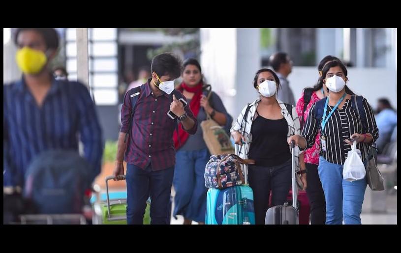 Passengers wear masks at Chennai airport. Photo: PTI
