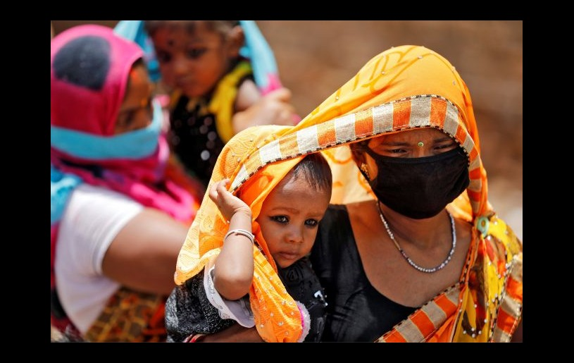 Migrant workers cover their children with saris, a traditional clothing worn by women, to protect them from heat as they wait to get on a bus to reach a railway station to board a train to their home state of eastern Bihar, during an extended lockdown to slow the spreading of the coronavirus disease (COVID-19), in Ahmedabad, India, May 20, 2020. REUTERS