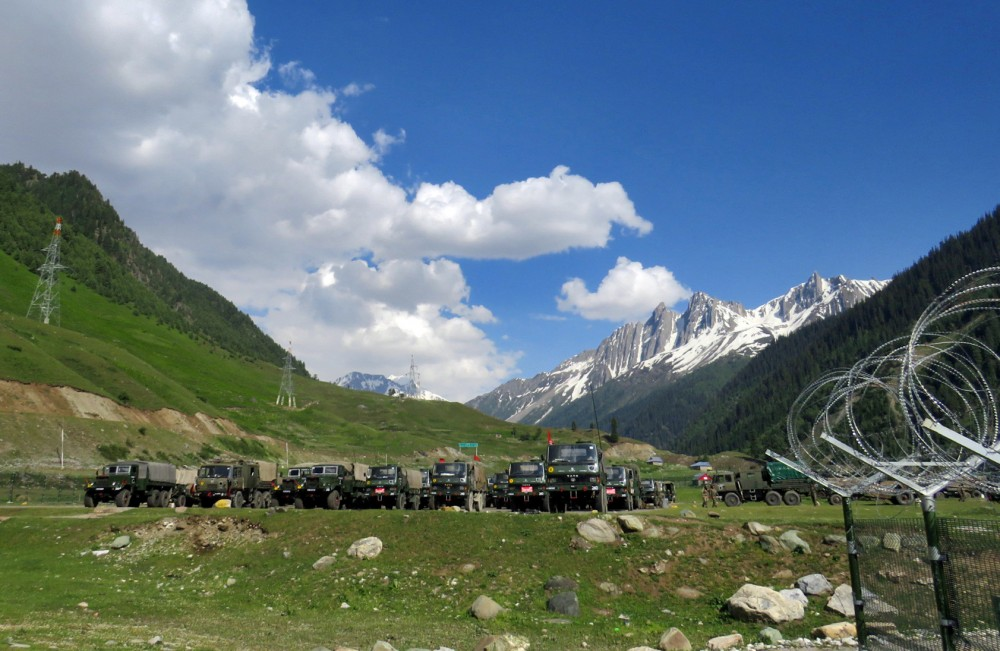 Indian army soldiers walk past their parked trucks at a makeshift transit camp before heading to Ladakh, near Baltal, southeast of Srinagar on June 16. (REUTERS/Stringer)
