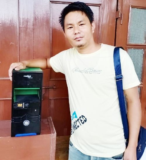 Self-taught electronics mechanic H. Tali Chang with the automatic contactless sanitizer dispenser unit which he developed with an assortment of electronic discards, which he donated to the Chang Baptist Church Mokokchung, June 27. (Morung Photo)