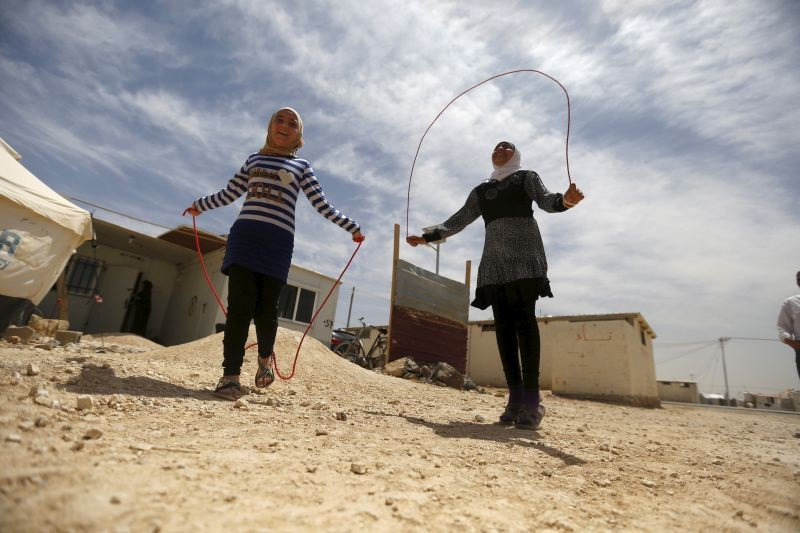 Syrian refugee Omayma al Hushan (R), 14, who launched an initiative against child marriage among Syrian refugees, plays with her friend outside their residence in Al Zaatari refugee camp in the Jordanian city of Mafraq, near the border with Syria on April 21, 2016. (REUTERS File Photo)