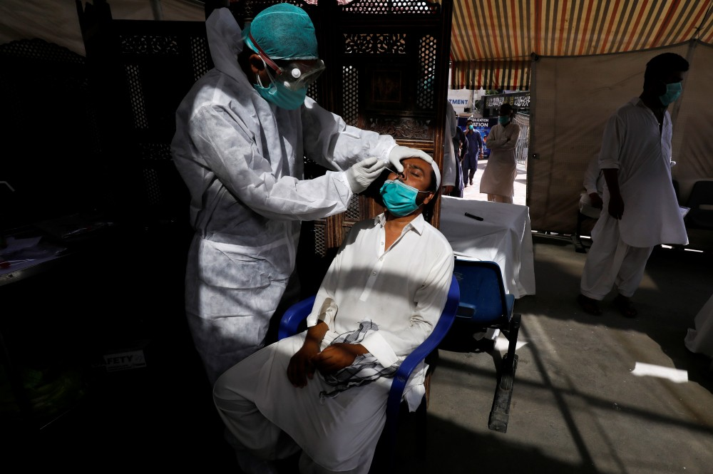 A paramedic wearing protective gear takes a nose-swab sample to be tested for the coronavirus disease (COVID-19), in Karachi, Pakistan on June 27. (REUTERS/Akhtar Soomro)