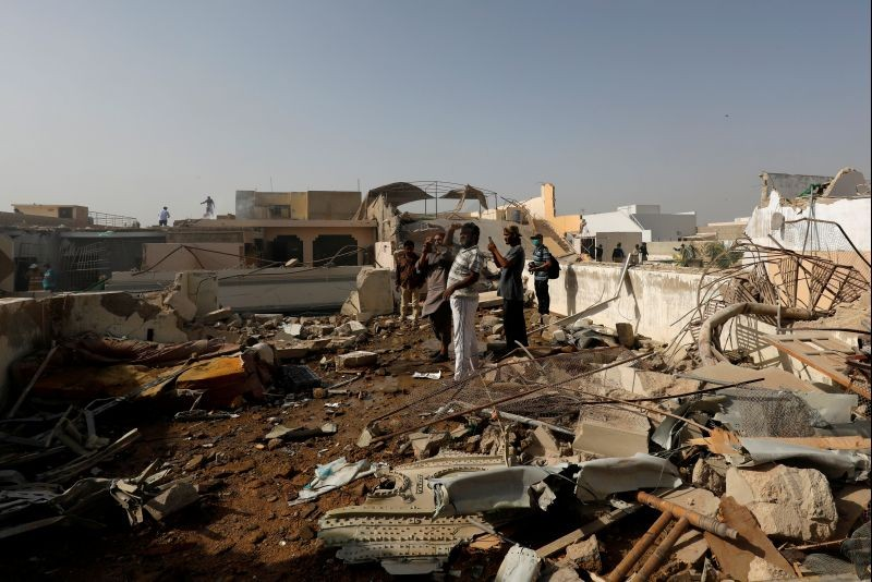 People stand on a roof of a house amidst debris of a passenger plane, crashed in a residential area near an airport in Karachi, Pakistan on May 22, 2020.( REUTERS File Photo)