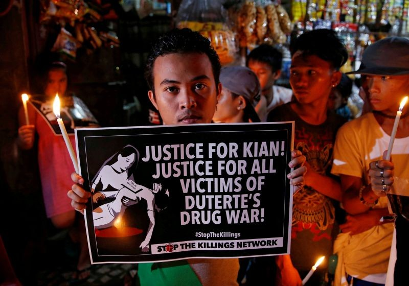 Protesters and residents hold lighted candles and placards at the wake of Kian delos Santos, a 17-year-old high school student, who was among the people shot dead in an escalation of President Rodrigo Duterte's war on drugs in Caloocan city, Metro Manila, Philippines on  August 25, 2017. (REUTERS File Photo)