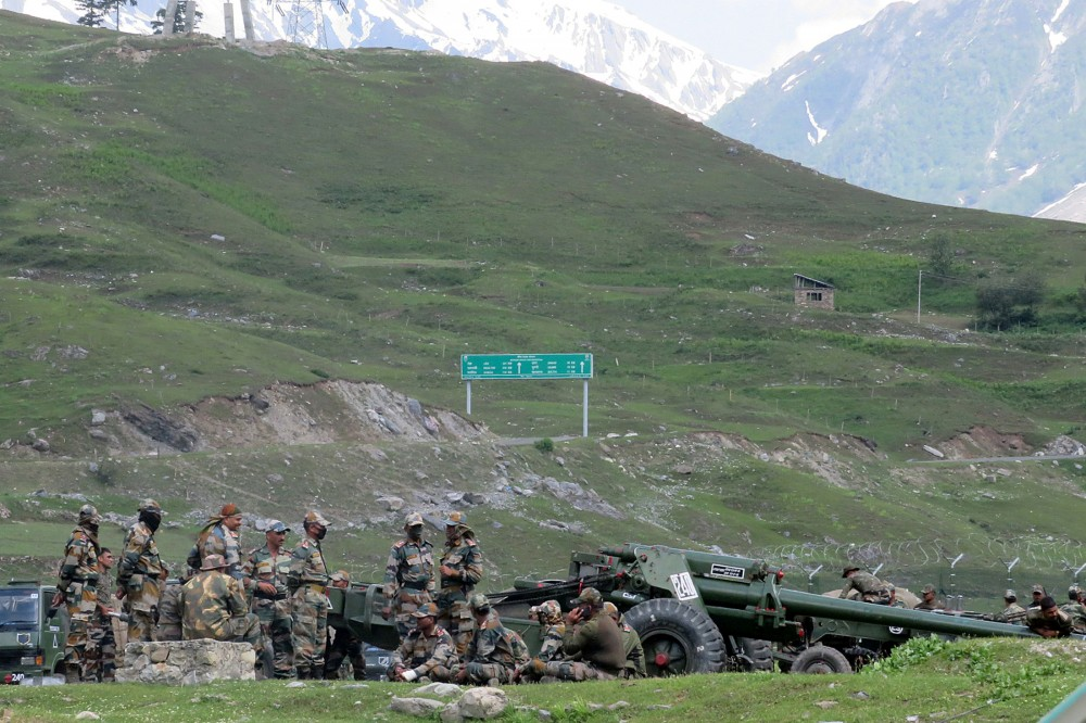 Indian army soldiers rest next to artillery guns at a makeshift transit camp before heading to Ladakh, near Baltal, southeast of Srinagar on June 16. (REUTERS/Stringer)