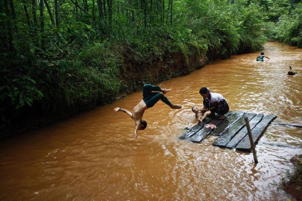 An ethnic Pa-O boy dives into the stream while his mother bathes a baby near Inle lake in Shan state, one of Myanmar's main tourist attractions, September 26, 2013. REUTERS/Minzayar