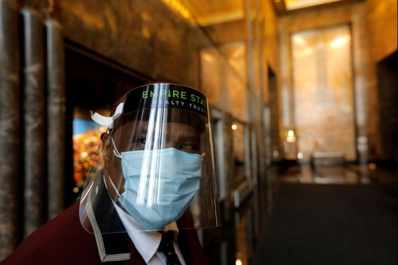 An employee wears a protective face mask and face shield in the main lobby of the Empire State Building in midtown Manhattan, as the iconic tower prepares to open to more tenants and visitors following the outbreak of the coronavirus disease (COVID-19) in New York City, New York, US on June 24, 2020. (REUTERS Photo)