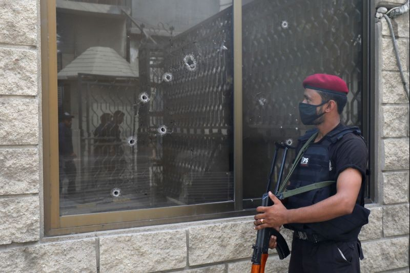 A police officer stands guard next to a bullet riddled window at the Pakistan Stock Exchange building after an attack in Karachi, Pakistan on June 29, 2020. (REUTERS Photo)