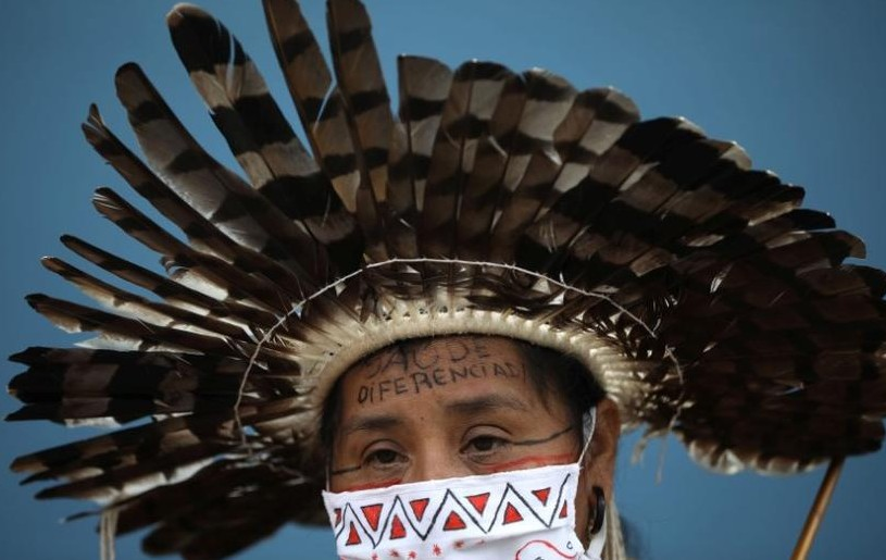 "Indigenous midwife Moy from Satere Mawe ethnicity, attends a protest demanding the entrance of traditional healers and better medical care at the Hospital Nilton Lins, which inaugurated a exclusive area for indigenous people to be treated from the coronavirus disease (COVID-19) in Manaus, Brazil June 3, 2020. The message on her forehead reads ""Differentiated Health"". REUTERS/Bruno Kelly"