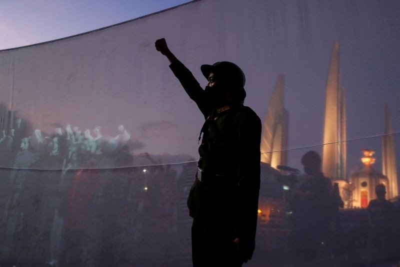 A demonstrator dressed with a vintage uniform raises his fist next to images of the 1932 coup in Thailand being projected on a white screen placed by protesters in front of the democracy monument as they demand a change in the constitution on the 88th anniversary of a revolt that ended the absolute monarchy in the country, in Bangkok, Thailand on June 24. (REUTERS Photo)