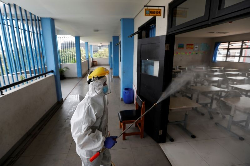 An Indonesian Red Cross personnel wearing a protective gear sprays disinfectant inside a classroom of a school after the government eased restriction measures amid the coronavirus disease (COVID-19) outbreak in Jakarta, Indonesia on June 23, 2020. (REUTERS Photo)