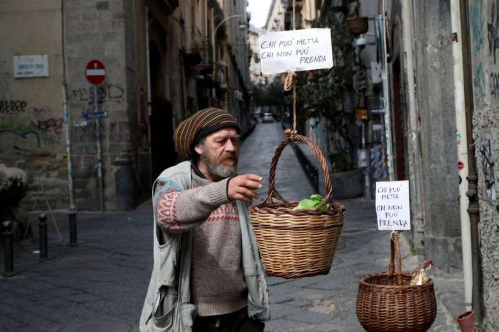 "A man reaches for a basket in Naples that was hung up so people can donate or take free food during the coronavirus outbreak. The sign reads: ""Who can puts in, who can't takes"" Photo taken Naples, Italy, March 30, 2020. REUTERS/Ciro De Luca"