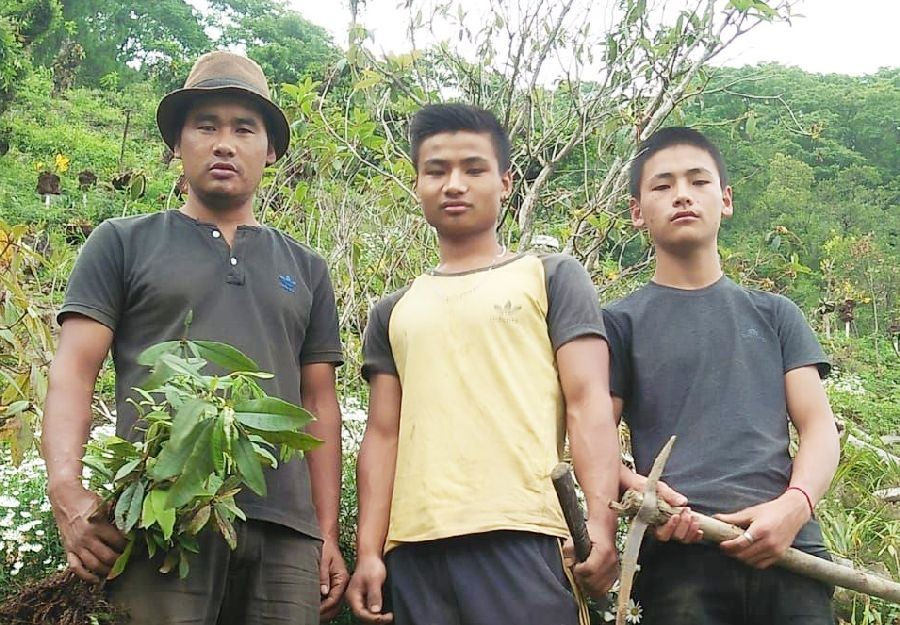 The three brothers against the backdrop of a 10 year old rhododendron tree, which was planted when Dr. Kelühol Tase was pursuing his graduation.