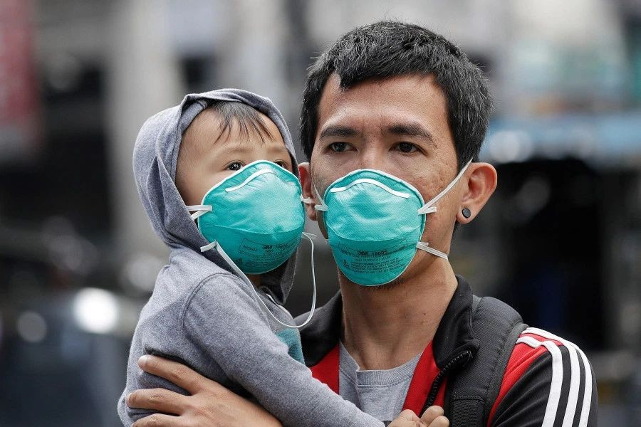 An adult and child wear flu masks in Manila, Philippines.  AP photo