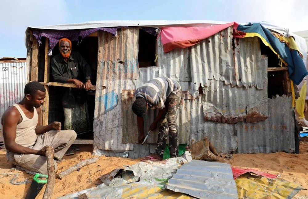 A man stands inside his makeshift shelter at a camp for the internally displaced people outside Mogadishu, Somalia August 28, 2018 REUTERS/Feisal Omar