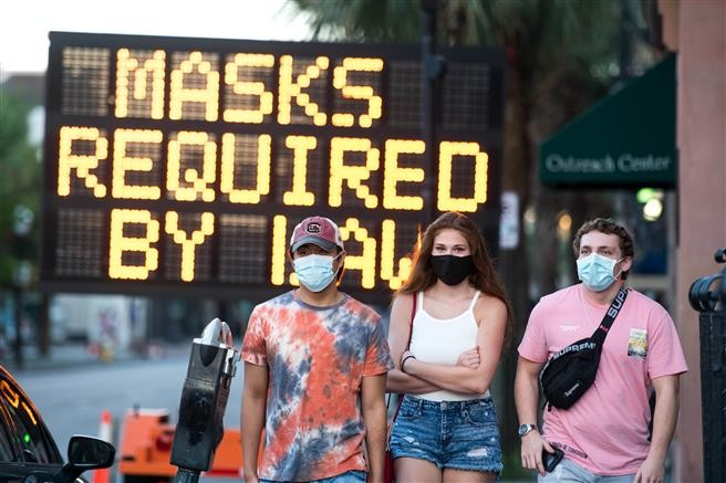 People wearing protective face masks walk along King St. in Charleston, South Carolina, on July 18, 2020. South Carolina is struggling with a high percentage of positive coronavirus test results. Getty Images/AFP