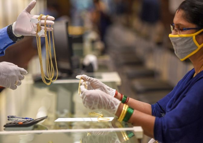 A salesman attends a customer at a jewellery shop, during Unlock 2.0, in Chennai, Saturday, July 11, 2020. (PTI Photo)