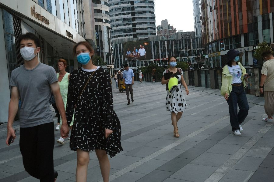 People wearing face masks are seen at the Sanlitun shopping area, following the outbreak of the coronavirus disease (COVID-19), in Beijing, China July 1, 2020. REUTERS/Tingshu Wang