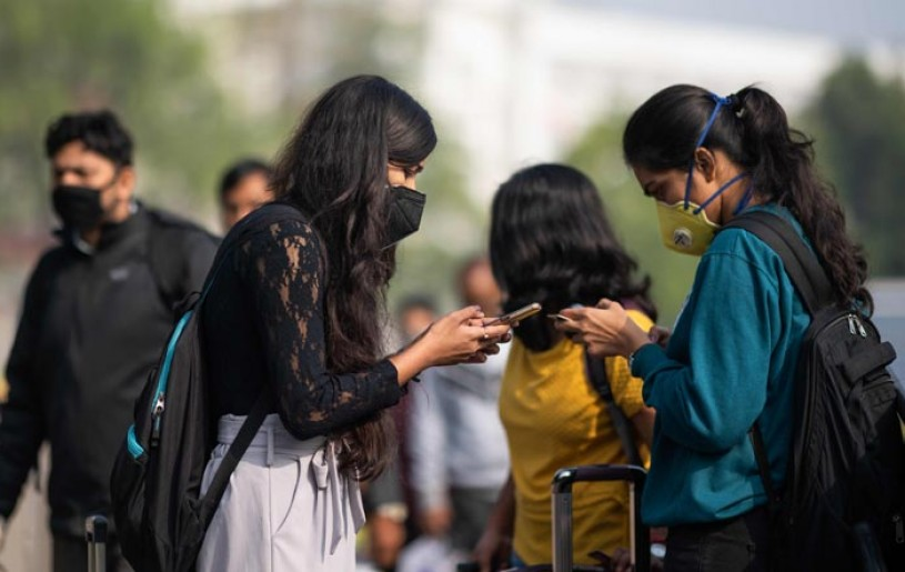 Women wearing facemasks as a preventive measure against the COVID-19 coronavirus use their mobile phones outside a metro station in New Delhi | AFP Photo