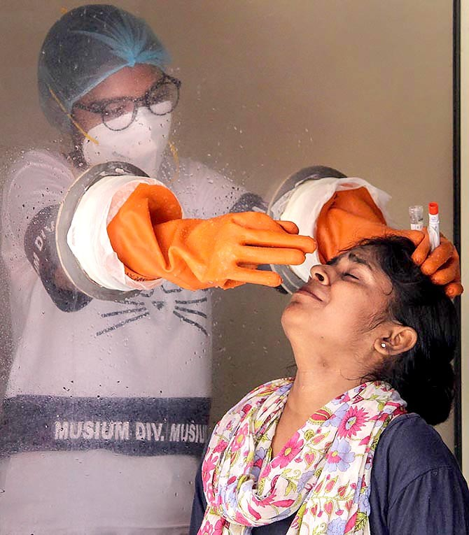 A health worker collects swab sample from a woman for COVID-19 Real-Time Polymerase Chain Reaction test in a containment zone in Gurugram. Photograph: PTI Photo