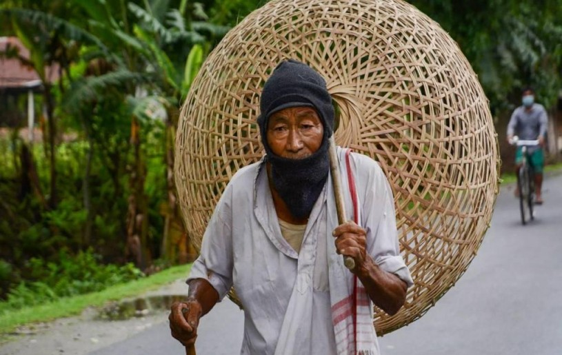An elderly man walks to a market to sell bamboo baskets during ongoing COVID-19 lockdown at Baganpara in Baksa district of Assam. (Photo | PTI)