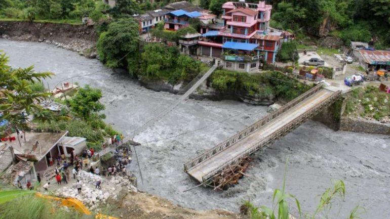 People gather near the bridge that is damaged due to the flood at Raghu Ganga River in Myagdi, Nepal July 11, 2020. REUTERS/Santosh Gautam