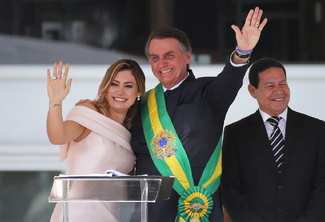 Brazil's President Jair Bolsonaro and his wife, Michelle Bolsonaro, wave during his speech at the Planalto Palace, in Brasilia. PHOTO: REUTERS/FILE