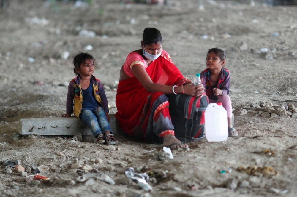 A migrant worker sits with her children as they wait to cross the border to their home state of Uttar Pradesh during a nationwide lockdown to slow the spread of the coronavirus disease in New Delhi, India, May 17, 2020. REUTERS/Adnan Abidi
