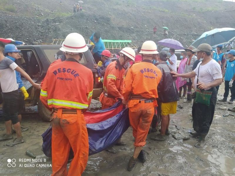 Rescue workers carry a dead body following a landslide at a mining site in Hpakant, Kachin State City, Myanmar July 2, 2020, in this picture obtained from social media. MYANMAR FIRE SERVICES DEPARTMENT/via REUTERS