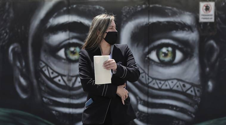 A woman wearing a face mask amid the spread of the new coronavirus walks past a mural of an Indigenous man in Bogota, Colombia. (AP Photo)